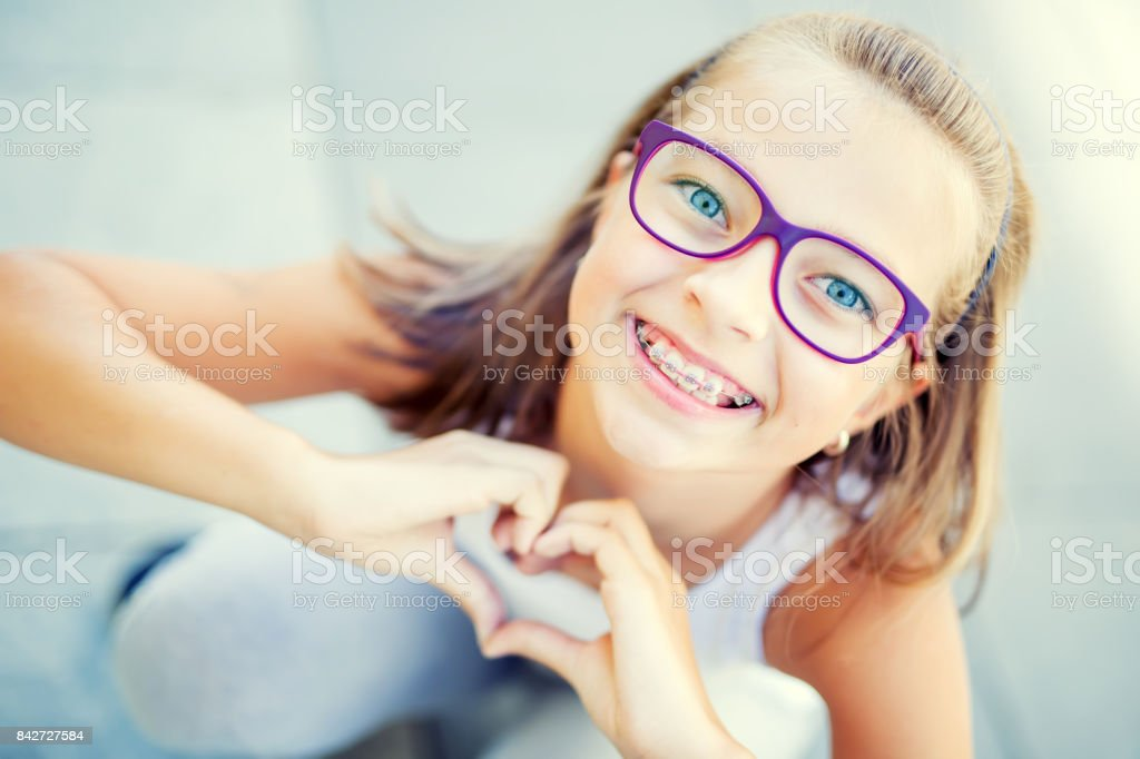Smiling little girl with dental braces and glasses showing heart with hands стоковое фото