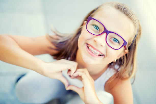 Smiling little girl with dental braces and glasses showing heart with hands stock photo