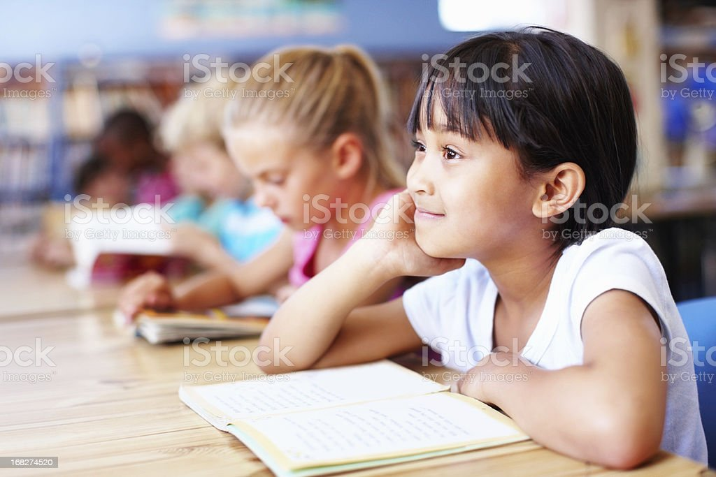 Smiling, little girl with friends studying in the library royalty-free stock photo