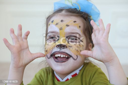 Close-up of smiling little girl with her face painted like a cheetah. Shallow depth of field.