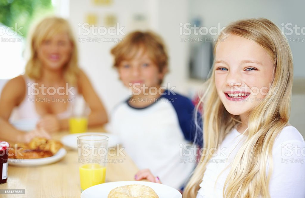 Smiling little girl with her family having breakfast royalty-free stock photo