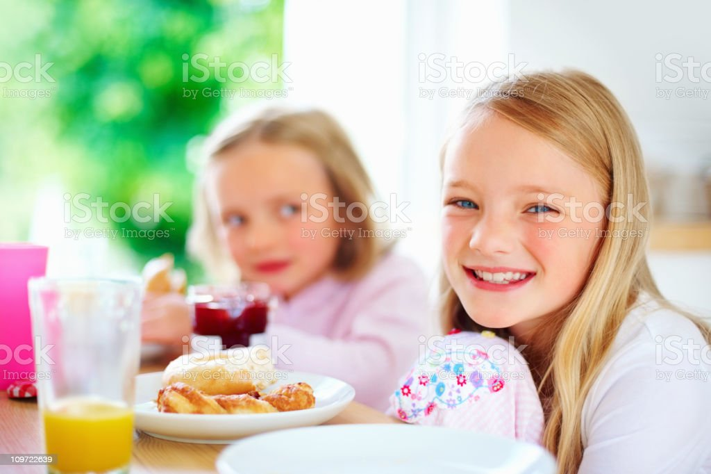 Smiling little girl with her sister having breakfast royalty-free stock photo