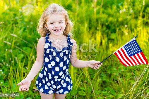 537898300istockphoto Smiling little girl with long curly hair holding american flag 479138744