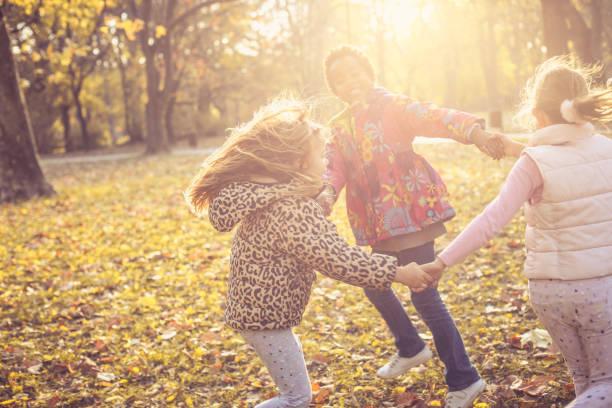 lächelnde mädchen im park. - sich im kreis drehen stock-fotos und bilder