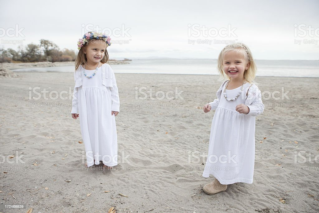 Smiling Little Girls Wearing White Dresses Playing on Beach royalty-free stock photo