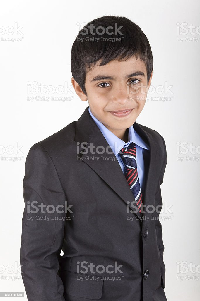 Smiling little mixed race boy in businessman suit stock photo