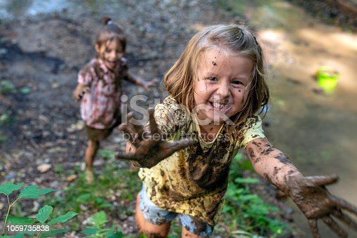 Smiling little muddy girl looking at camera and showing palms to a photographer.
