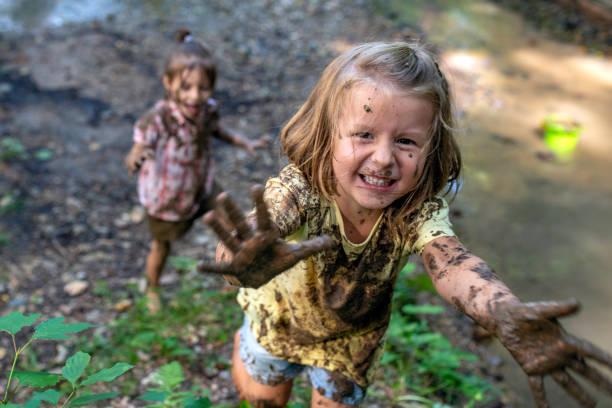 lachende modderige meisje - bos spelen stockfoto's en -beelden
