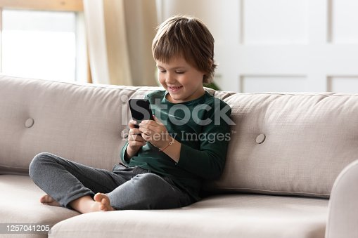 Smiling little preschool child boy playing online game, watching video on cellphone, entertaining alone in living room. Happy small kid using funny mobile apps, enjoying free leisure time at home.