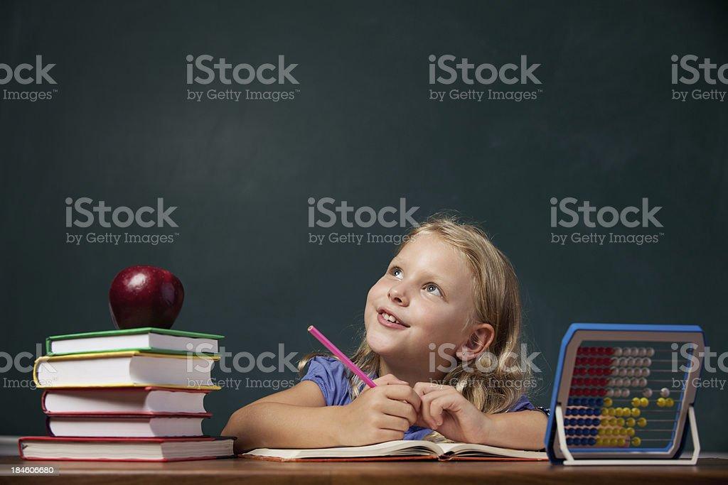 Smiling little school girl thinking on desk before blackboard royalty-free stock photo