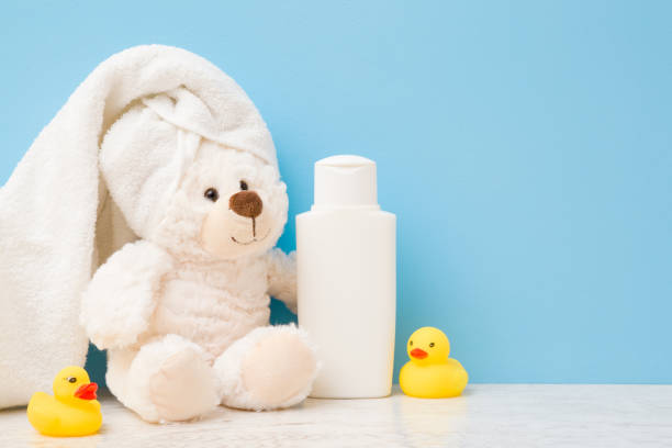 Smiling, lovely white teddy bear sitting. Towel on head. Yellow rubber ducks and shampoo bottle on shelf. Children bathing concept. Empty place for text on light blue wall. Pastel color. Closeup. Smiling, lovely white teddy bear sitting. Towel on head. Yellow rubber ducks and shampoo bottle on shelf. Children bathing concept. Empty place for text on light blue wall. Pastel color. Closeup. kids cleaning up toys stock pictures, royalty-free photos & images