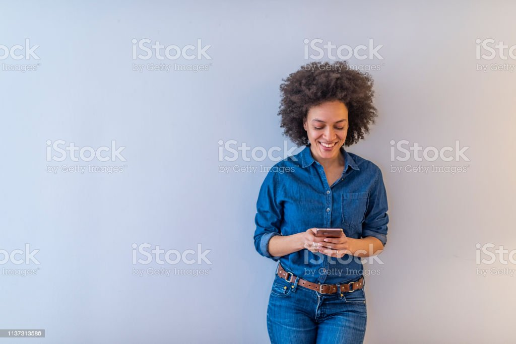 Smiling lovely young woman standing and using cell phone over grey background royalty-free stock photo