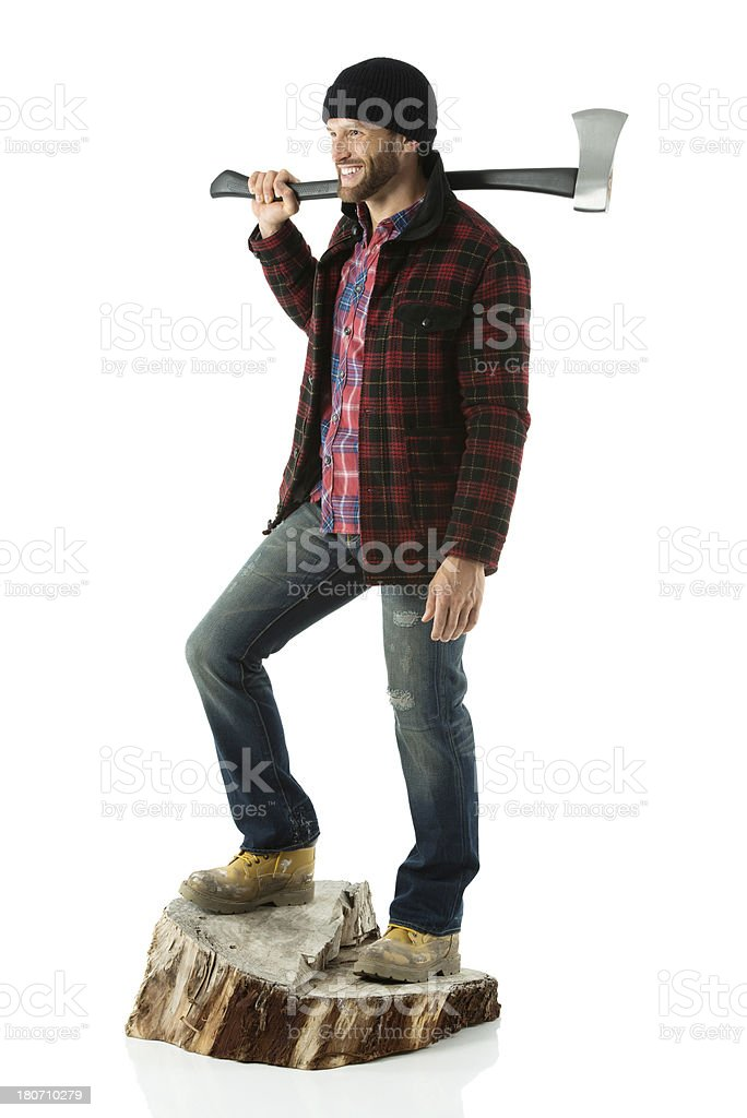 Smiling lumberjack standing on tree stump with axe royalty-free stock photo