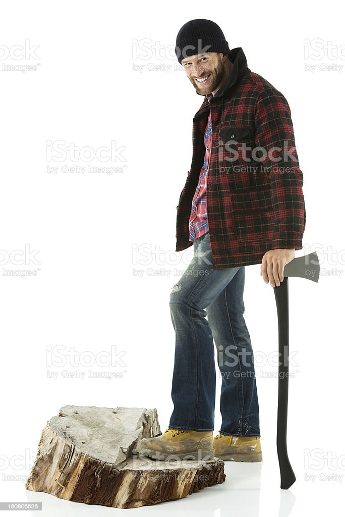 Smiling lumberman standing on wood log with an axe royalty-free stock photo