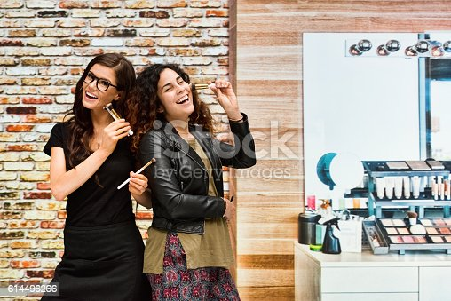 620404536istockphoto Smiling make up artist and client together 614496266