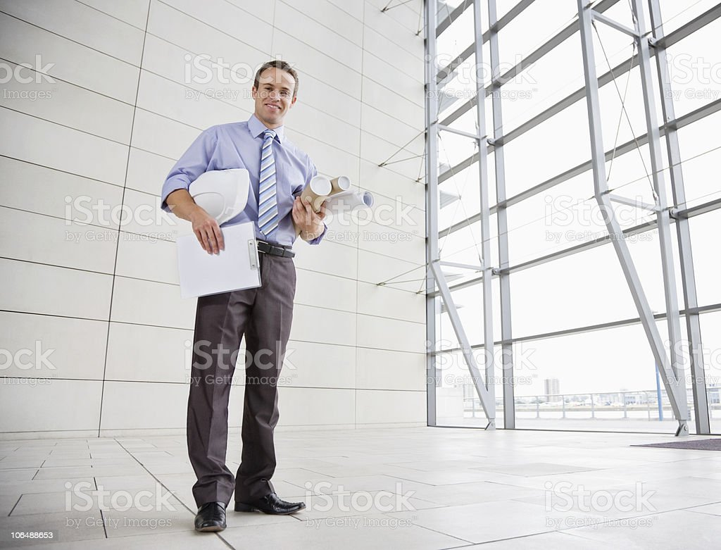 Smiling male architect with hardhat and rolled blue prints royalty-free stock photo