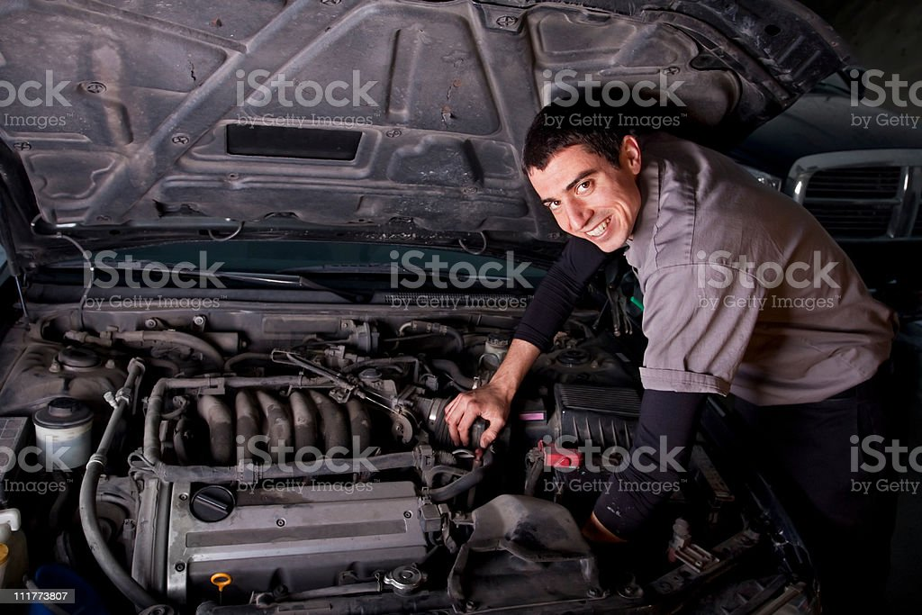Smiling male auto repair mechanic works on an engine stock photo