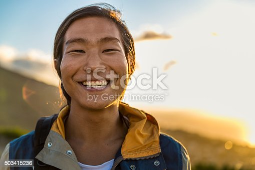 A photo of smiling male backpacker on hill. Happy traveler is in jacket. Portrait of man is enjoying vacation against sky during sunset.