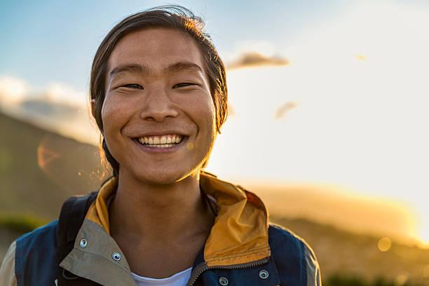 sonriente hombre mochilero en hill durante la puesta del sol - etnia fotografías e imágenes de stock