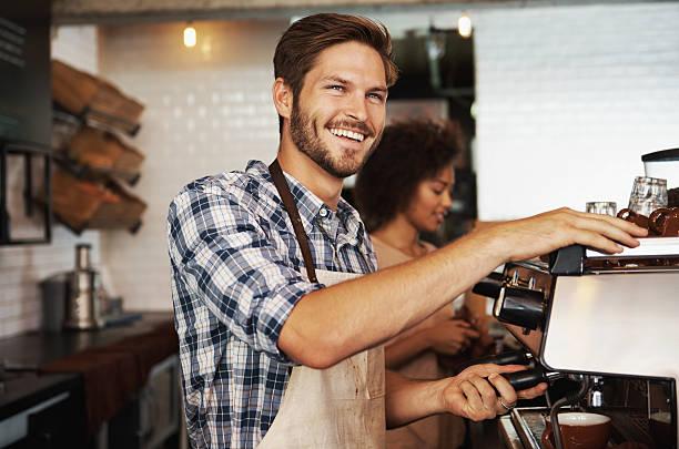Smiling male barista preparing coffee stok fotoğrafı