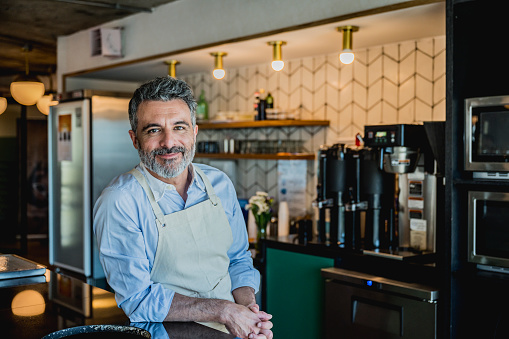 Bearded barista wearing apron and leaning on counter of corporate coffee bar in Buenos Aires office and smiling at camera.