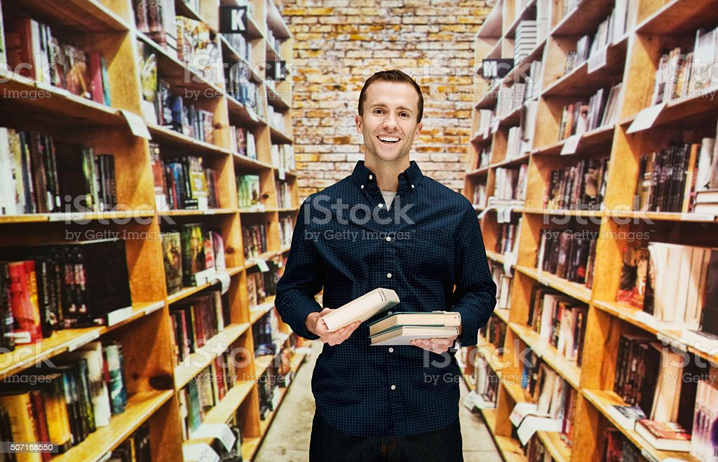 Smiling male bookseller in library stock photo