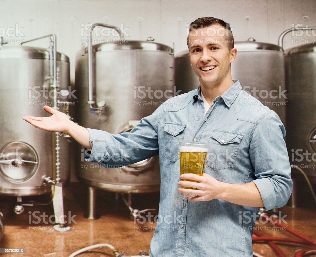 Smiling male brewmaster presenting in brewery stock photo