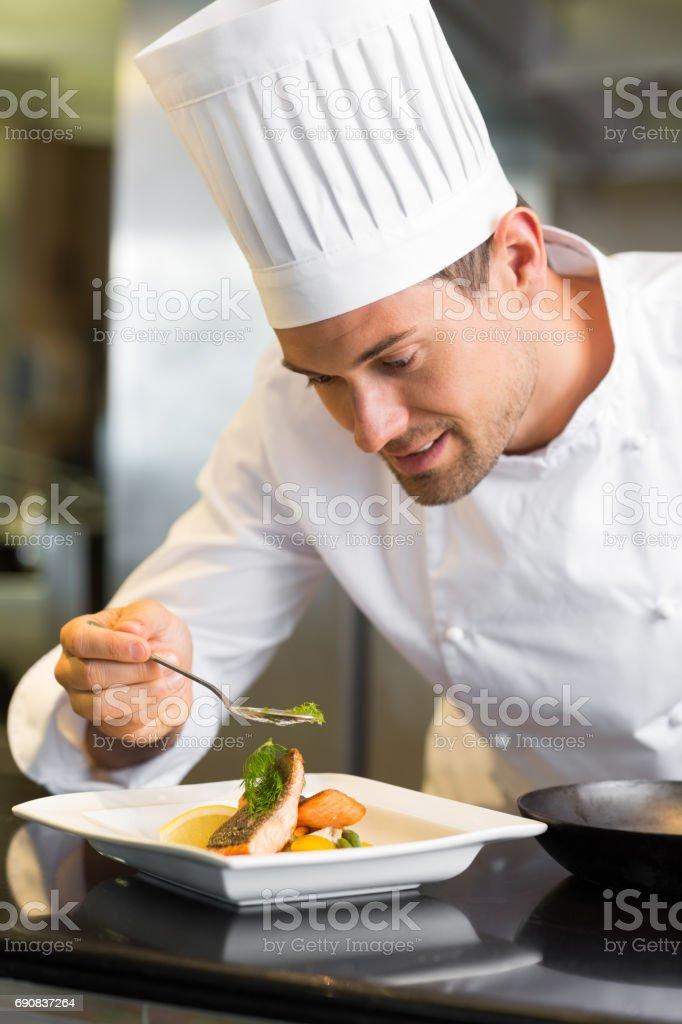 Souriant le chef mâle nourriture saisie-arrêt dans cuisine - Photo