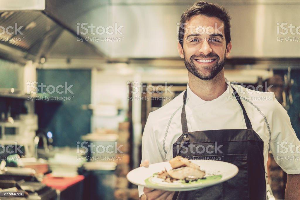 Lächelnd männlichen Chef hält zubereitet Gericht in Küche – Foto