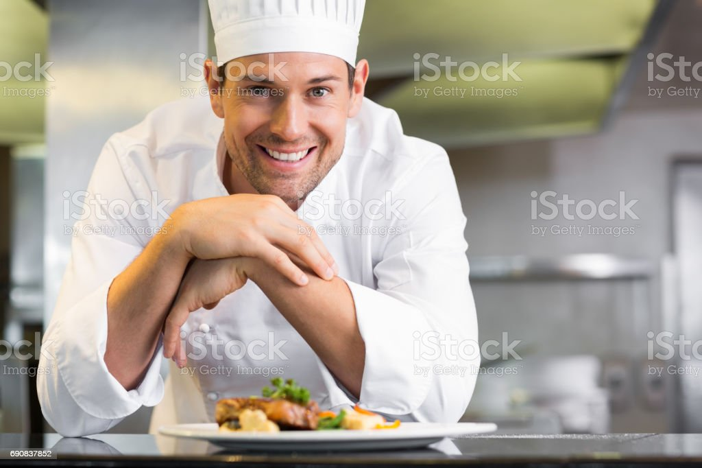 Smiling male chef with cooked food in kitchen stock photo