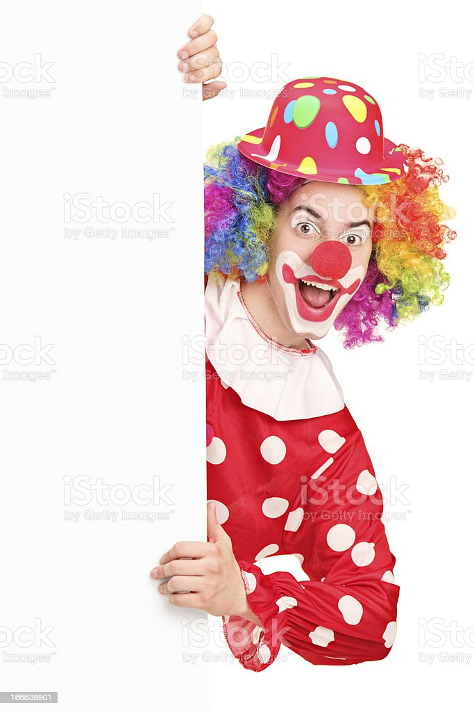 Smiling male clown posing behind a panel royalty-free stock photo