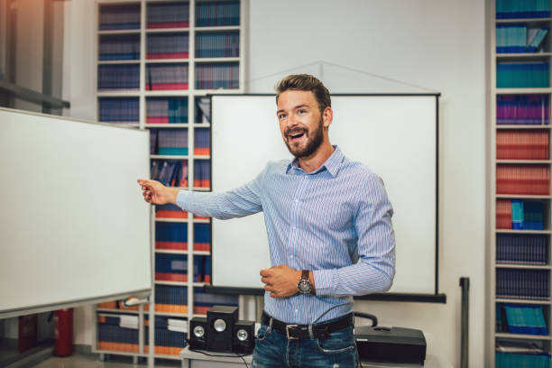 Smiling male coach giving presentation for audience in lecture hall stock photo