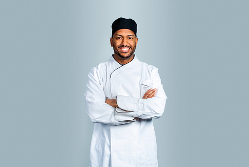 Smiling male cook standing with hands folded. Portrait of confident chef in uniform against gray background.