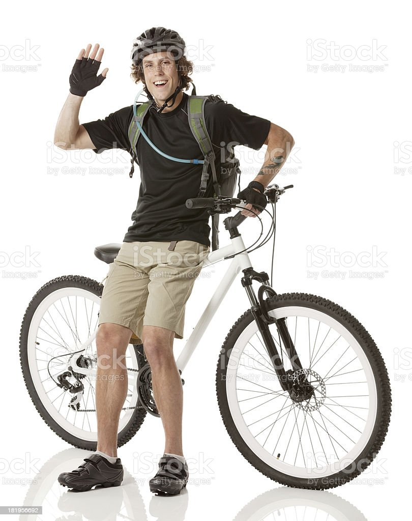 Smiling male cyclist waving his hand royalty-free stock photo