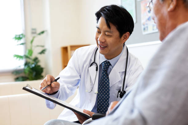 Smiling male doctor discussing over medical record with senior man in hospital stock photo