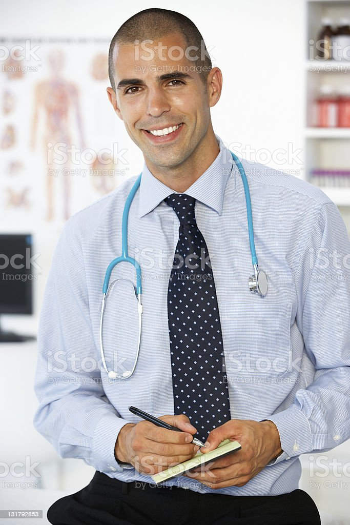 A smiling male doctor writing a prescription royalty-free stock photo
