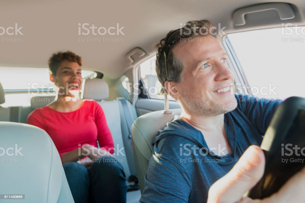 Smiling Male Driver Gives Ride to Smiling Passenger in Backseat stock photo