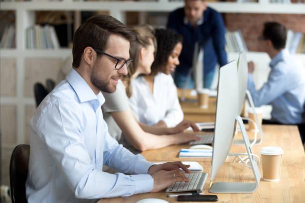 微笑的男性員工在辦公室的個人電腦上發短信 - 中等人數群 個照片及圖片檔