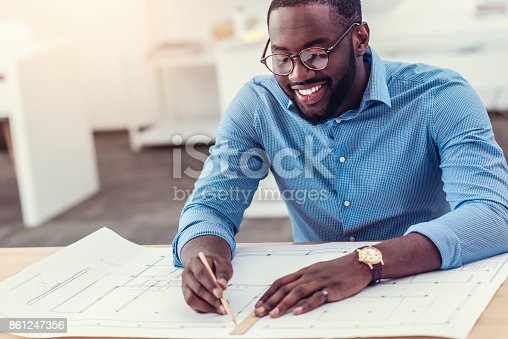 istock Smiling male engineer working on technical drawing at table 861247356