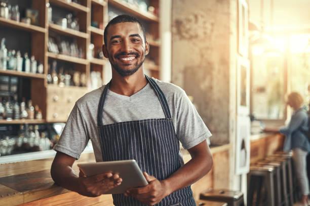 un empresario masculino sonriente en su cafetería sosteniendo la pestaña digital - sólo hombres jóvenes fotografías e imágenes de stock