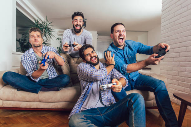 Smiling male friends playing video games at home and having fun. Smiling male friends playing video games at home and having fun. man cave stock pictures, royalty-free photos & images