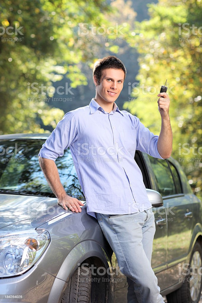 Smiling male holding a car key royalty-free stock photo