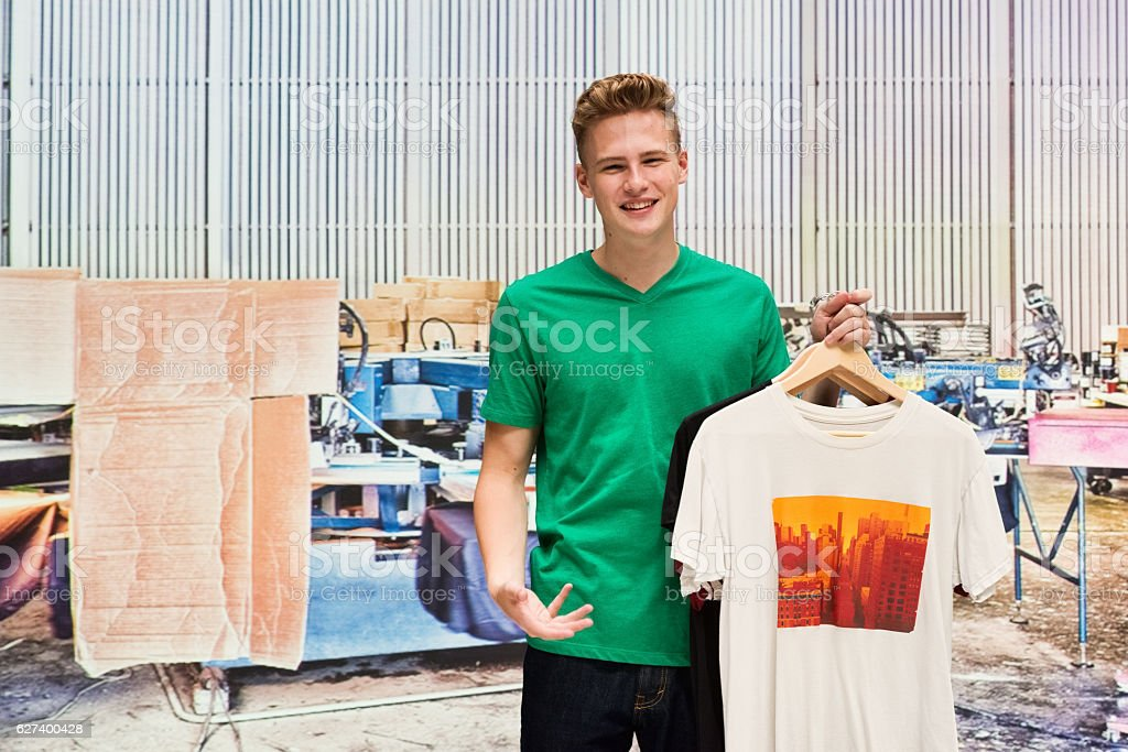 Smiling male holing t-shirt he printed stock photo