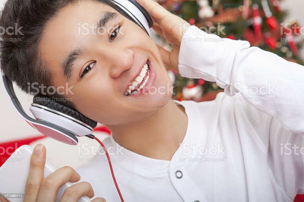 Smiling male listening to headphone at christmas royalty-free stock photo