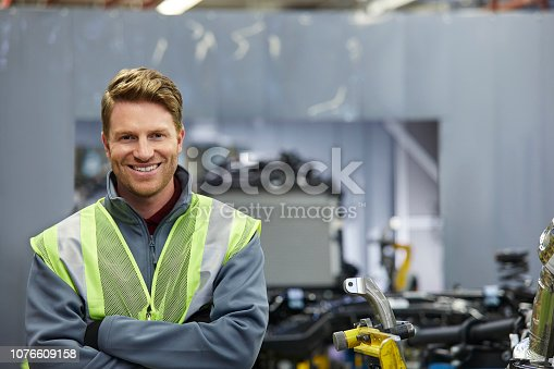 941796726istockphoto Smiling male mechanical engineer with arms crossed 1076609158