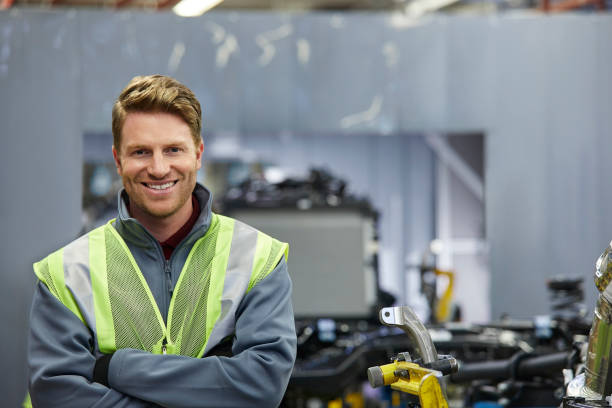 Smiling male mechanical engineer with arms crossed Smiling manager standing by car chassis at automobile industry. Portrait of confident male mechanical engineer is with arms crossed at factory. He is wearing reflective clothing. mechanical engineering stock pictures, royalty-free photos & images