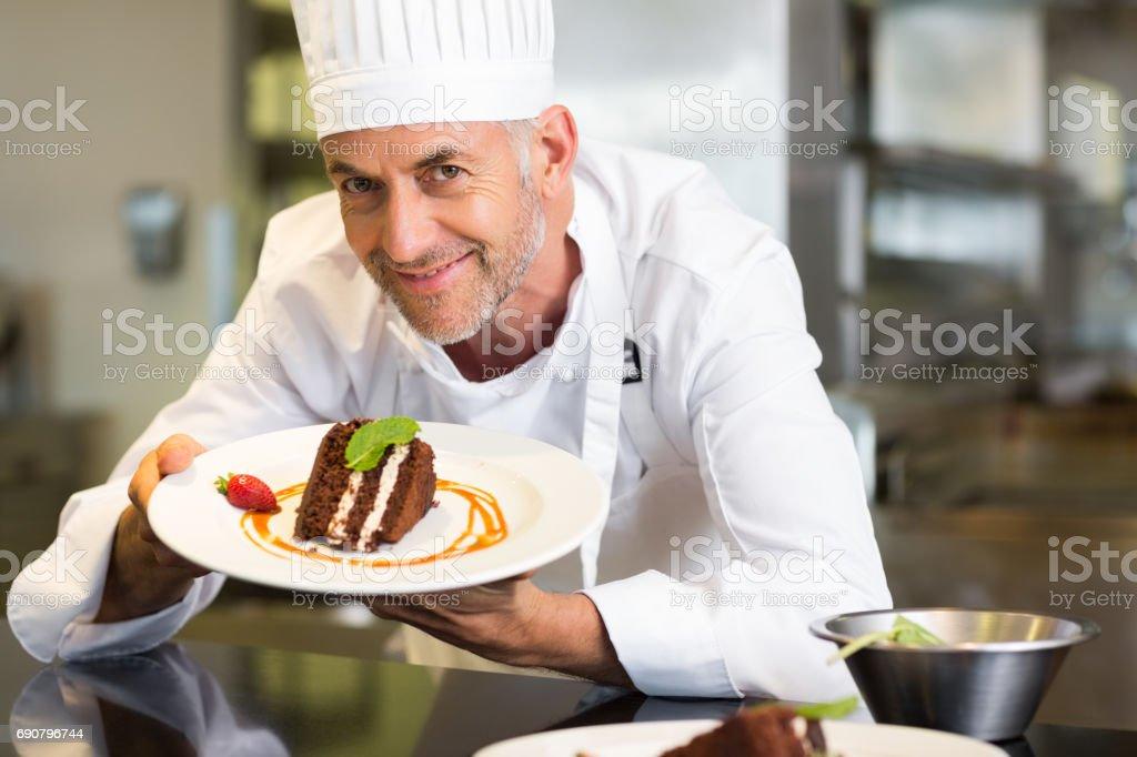 Souriant pâtissier mâle avec le dessert dans la cuisine - Photo