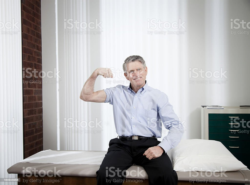 Smiling male patient at doctor office flexing arm for camera stock photo