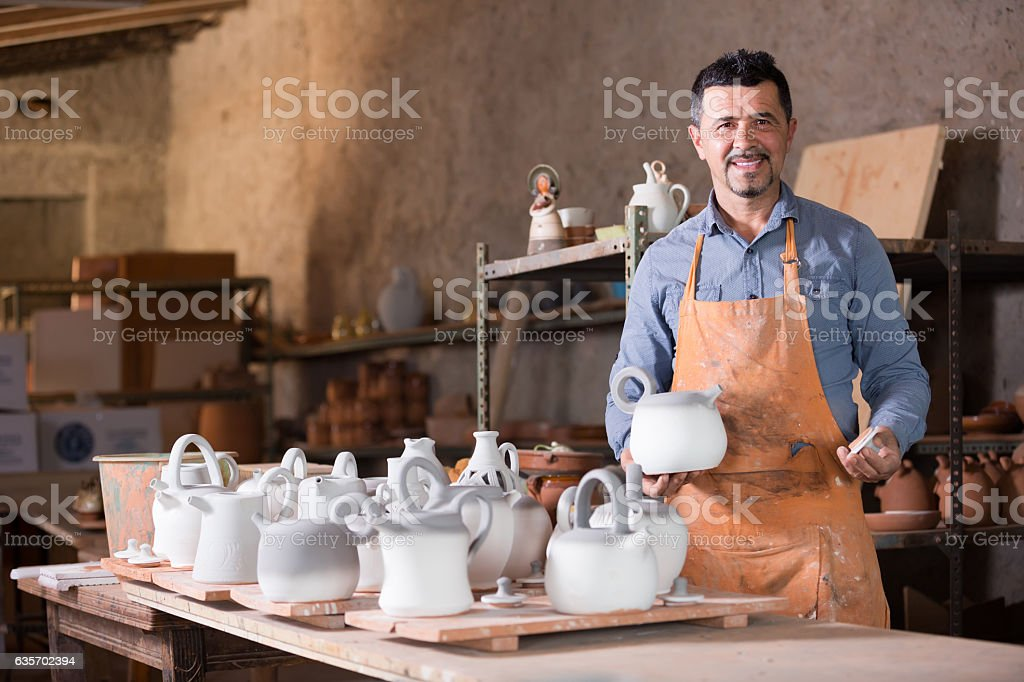 Smiling male sculptor having ceramics in hands royalty-free stock photo