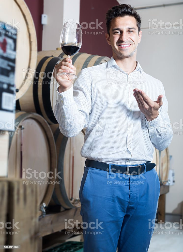 Smiling male seller holding glass of red wine in shop stock photo